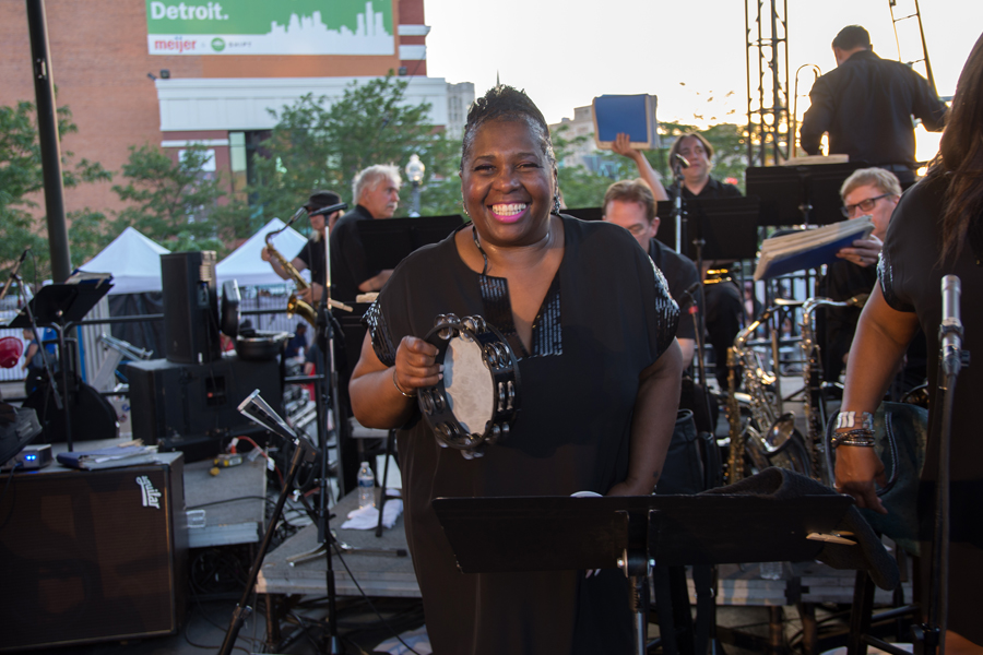 Smiling woman holds tambourine on stage with band